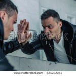 stock-photo-quite-wealthy-man-with-the-beaten-person-looks-at-themselves-in-a-mirror-and-looks-in-the-face-he-624222251