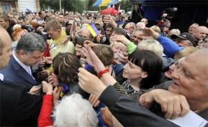 Шоколадовият магнат Петро Порошенко е най-вероятният победител на президентските избори в Украйна на 25 май. Той събира хиляди привърженици и в Източна Украйна. На снимката Порошенко (в ляво) е на митинг в град Никопол, близо до Днепропетровск.